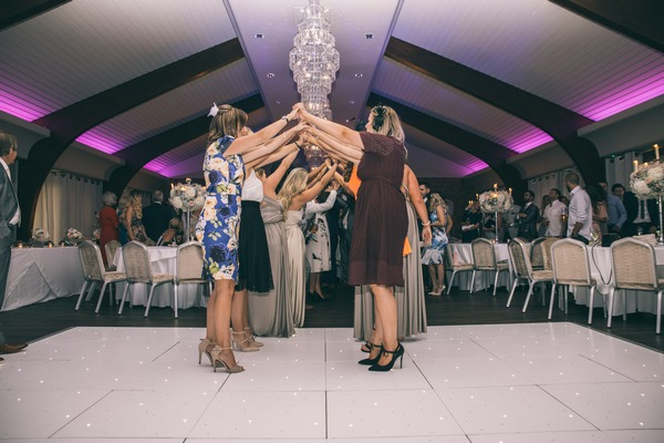Wedding guests making arch for bride and groom to walk through