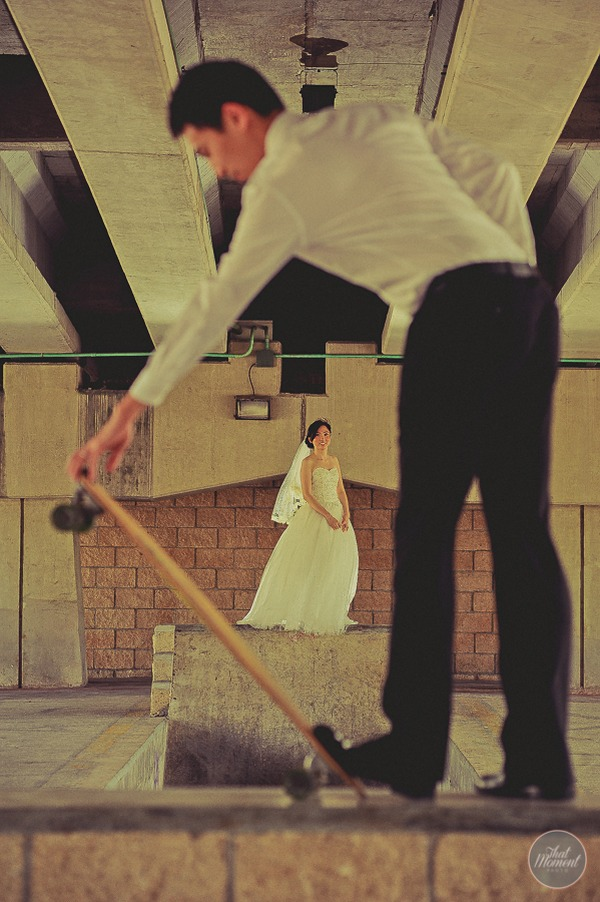 Groom flipping up skateboard as bride watches in background