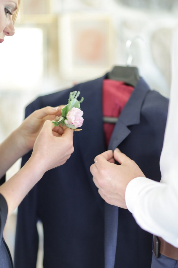 Bride holding groom's buttonhole