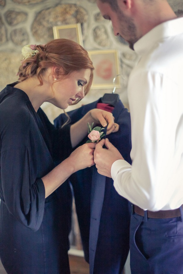 Bride helping groom attach buttonhole to jacket