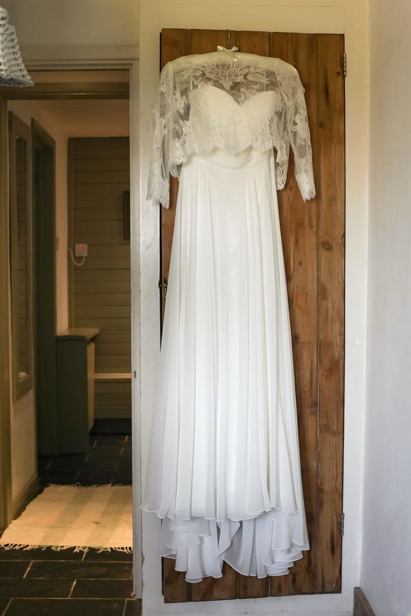 Lace wedding dress hanging on door