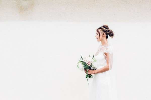 Bride standing holding bouquet against white background - Picture by Devin Ainslie Photography