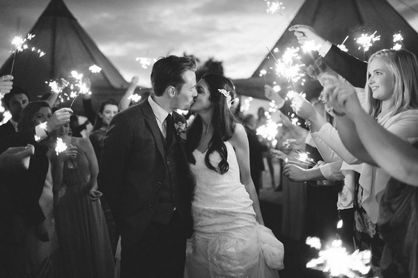 Bride and groom kissing surrounded by guests with sparklers - Picture by Frances Sales Photography