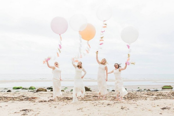Bride and bridesmaids holding balloons jumping on beach - Picture by Suzanne Li Photography