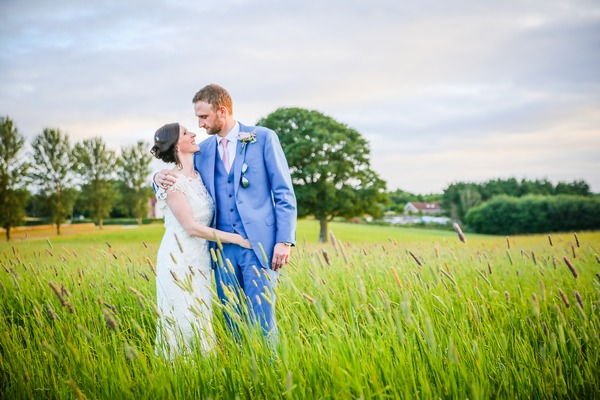 Bride and groom standing in a field looking into each others eyes - Picture by Danna Geen Photography