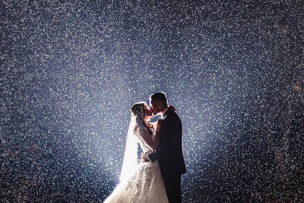 Bride and groom kissing in the rain - Picture by White Stag Wedding Photography