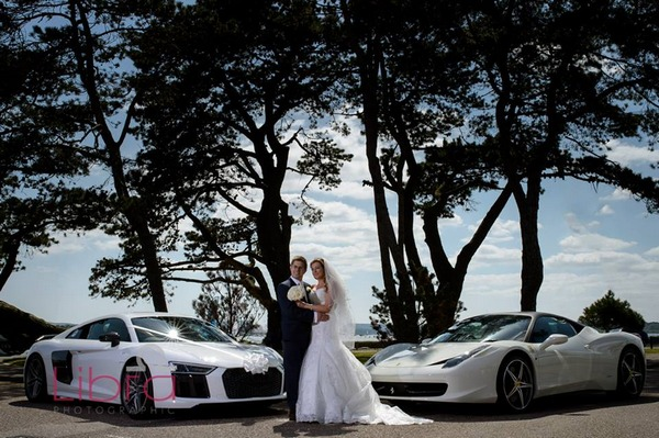 Bride and groom standing between two sports cars - Picture by Libra Photographic