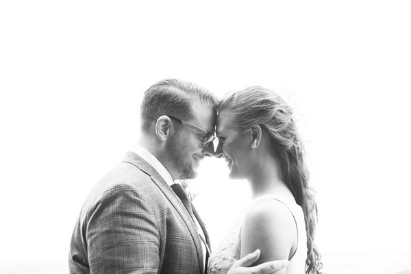 Bride and groom touching heads against white background - Picture by Gemma Christine Photography