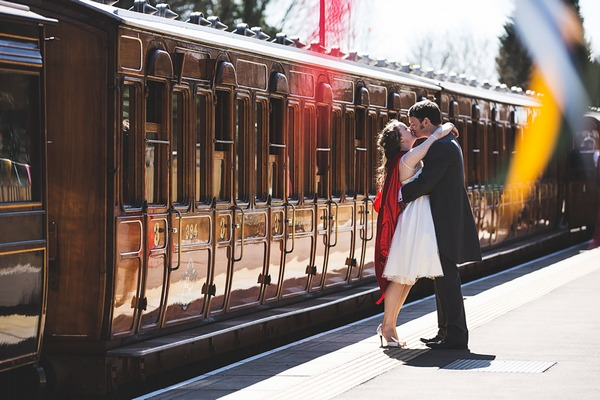 Bride and groom kissing next to train on platform - Picture by Cristina Rossi Photography