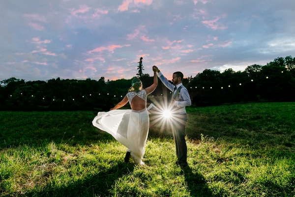Bride twirling on grass with groom - Picture by ELS Photography