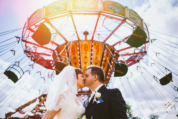 Bride and groom kissing under fairground ride - Picture by Clare Tam-Im Photography