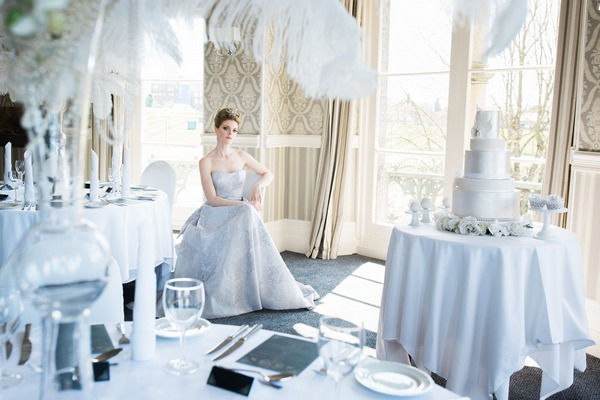 Bride sitting amongst wedding tables in The Duke of Cornwall Hotel
