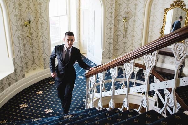 Groom walking up The Duke of Cornwall Hotel stairs