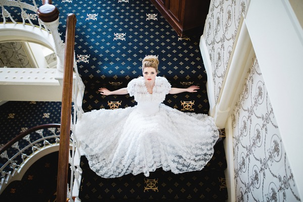 Bride sitting on of The Duke of Cornwall Hotel stairs