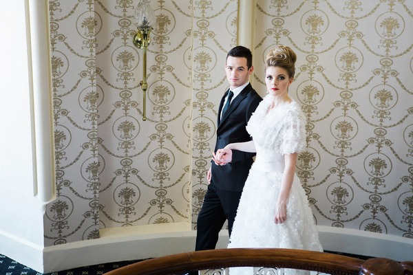 Bride and groom holding hands on The Duke of Cornwall Hotel stairs