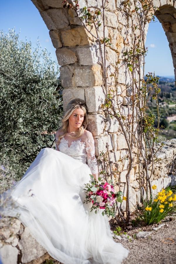 Bride sitting on wall