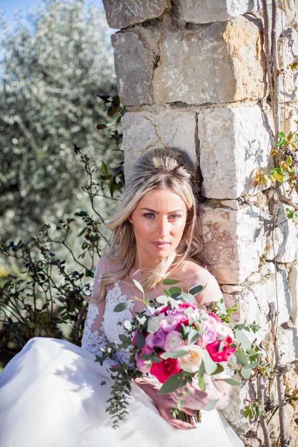 Bride sitting holding bouquet