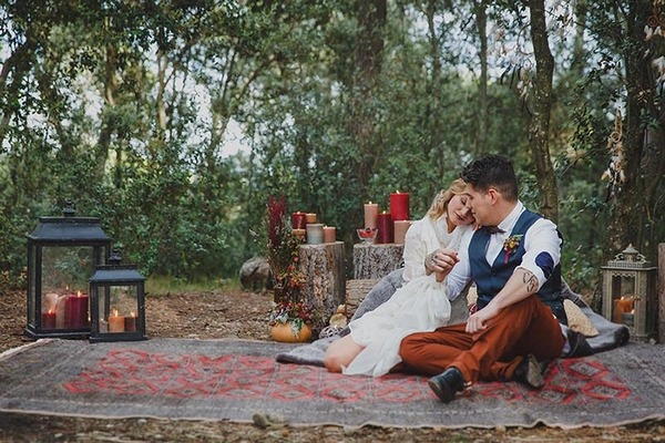 Bride and groom sitting on rug in woods