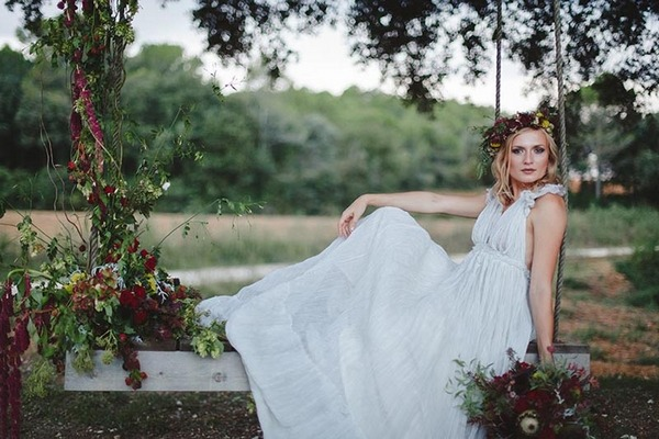 Boho bride sitting on swing with flowers