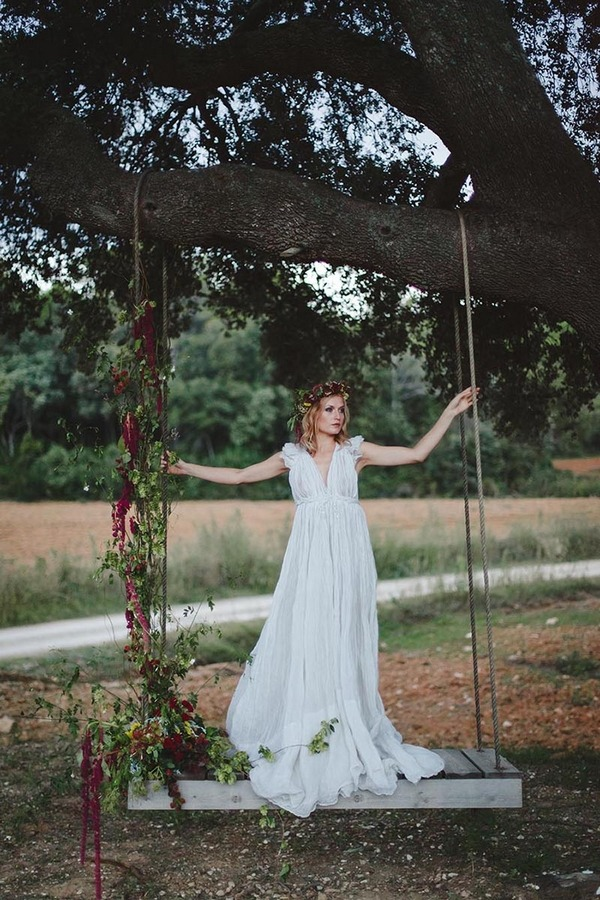Boho bride standing on swing