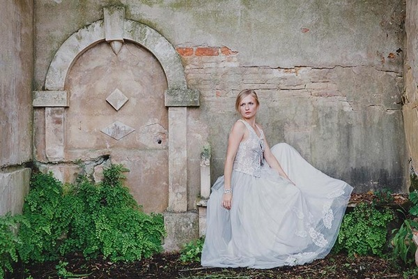Bride sitting by old fountain