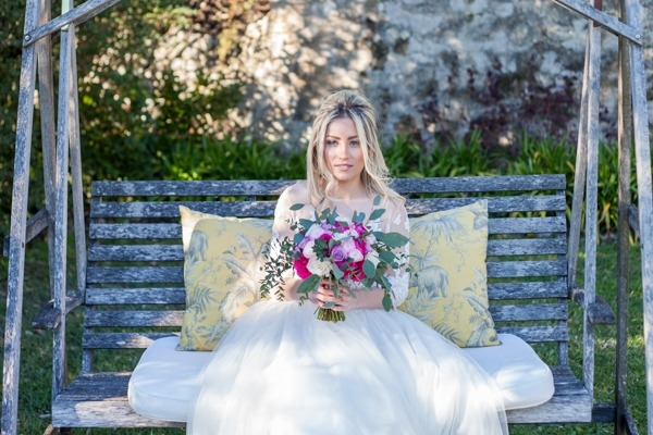 Bride sitting on bench holding bouquet