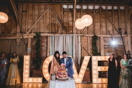 Couple cutting wedding cake with large illuminated letters behind them