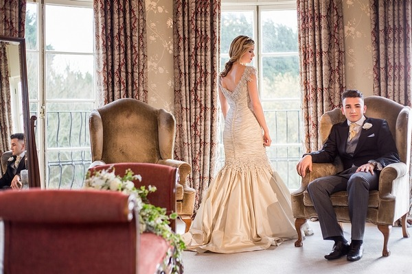 Bride and groom in bedroom at Wyck Hill House
