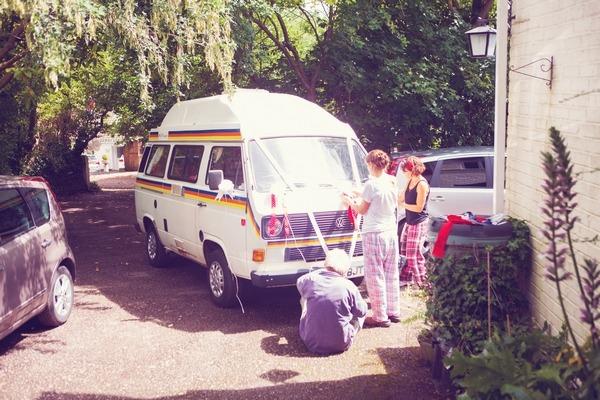 Guests putting ribbons on wedding camper van