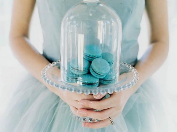 Bride holding macaroons under cloche