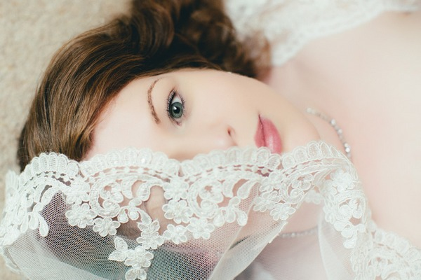 Bride laying on floor with veil covering half her face - Picture by Toni Darcy Photographer