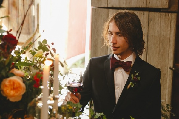 Groom holding glass of red wine