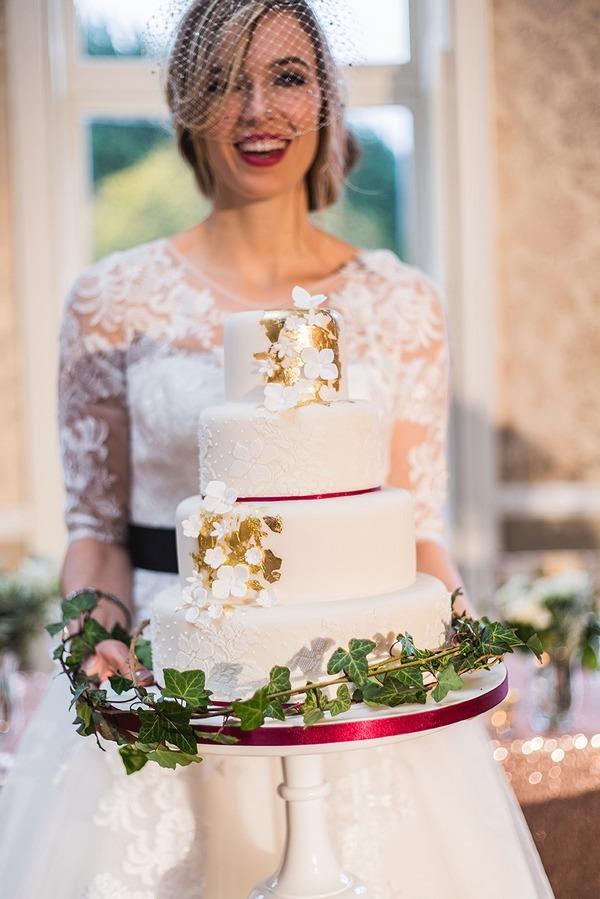 Bride holding winter wedding cake
