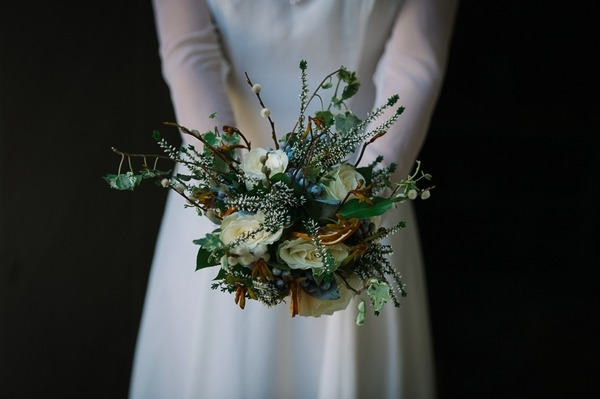 Bride holding out winter wedding bouquet