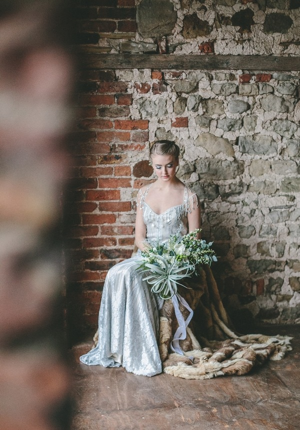 Bride sitting on chair looking down at bouquet