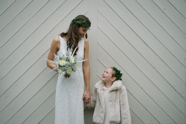 Bride and flower girl holding hands and looking at each other