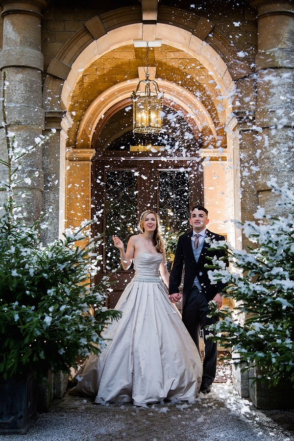 Bride and groom in snow outside Wyck Hill House
