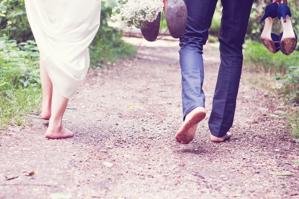 Bride and groom walking barefoot down path