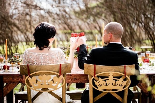 Bride and groom sitting raising toast