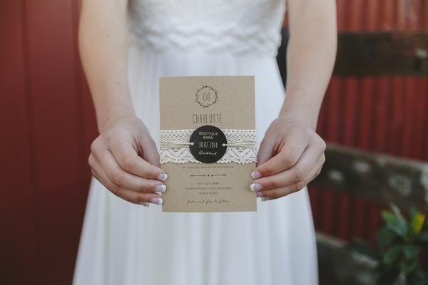 Bride holding rustic wedding invitation
