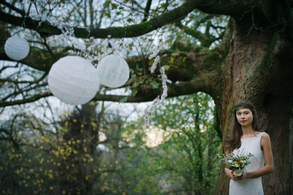 Bride standing by tree with hanging lanterns