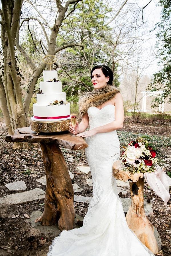 Bride wearing shrug standing next to of wedding cake