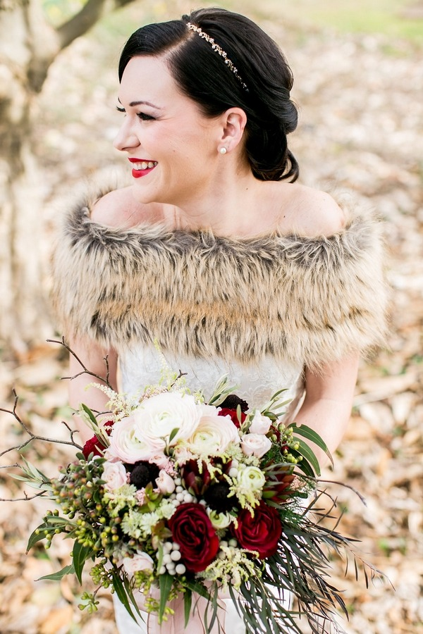 Bride with fur shrug and bouquet smiling