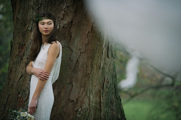 Bride standing by tree