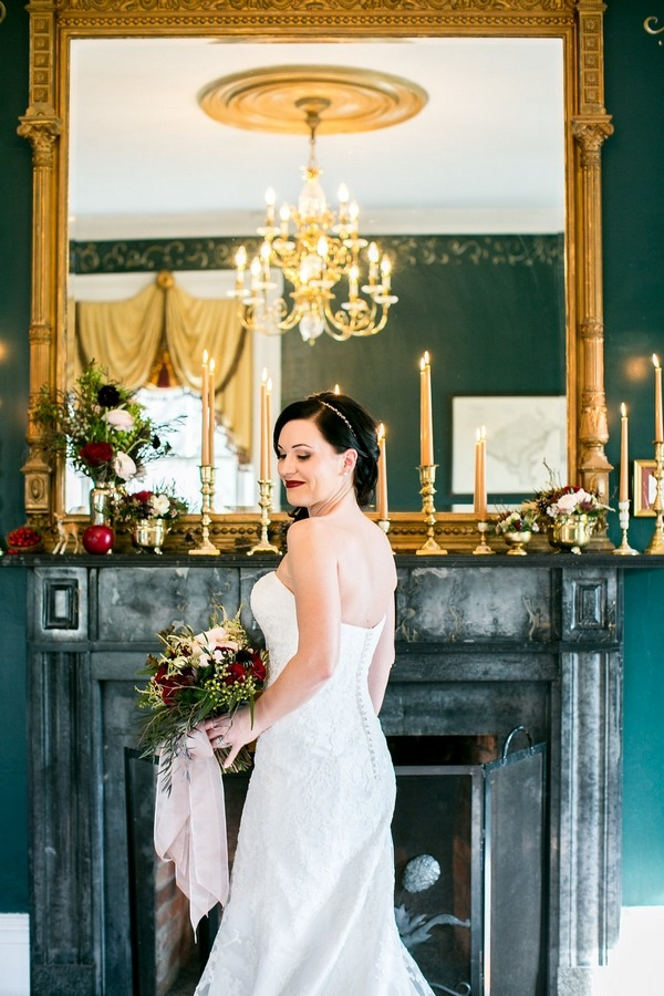 Bride standing in front of fireplace