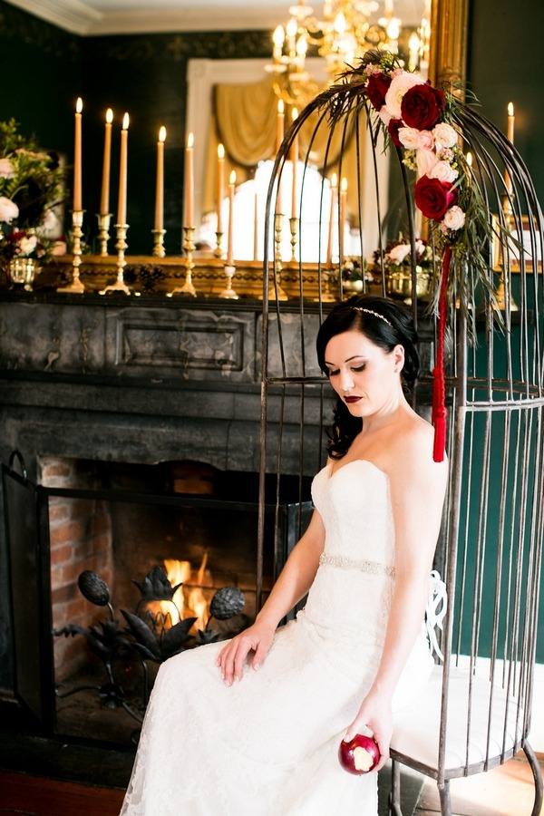 Bride sitting in birdcage swing chair by fire