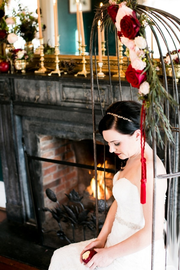Bride sitting in birdcage swing chair looking down