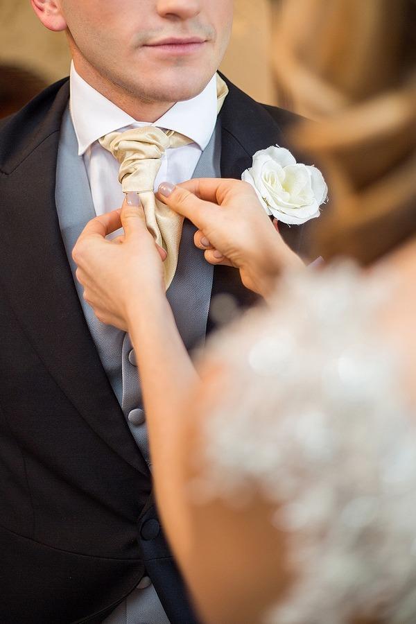 Bride adjusting groom's cravat