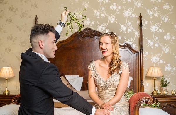 Groom holding mistletoe over bride