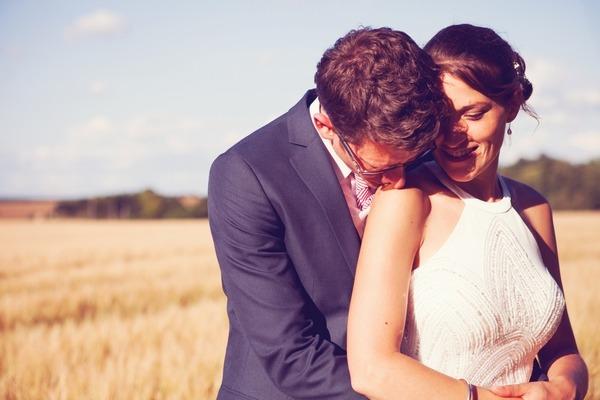 Groom kissing bride on the shoulder